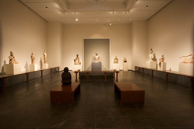 A woman sits alone in a room full of Buddhas at the Metropolitan Museum of Art.