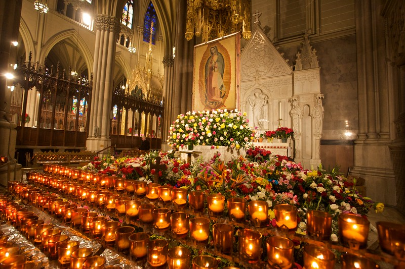 Flowers and candles arrayed before the icon of Our Lady of Guadalupe on 14th December 2009 for her feast-day three days earlier.