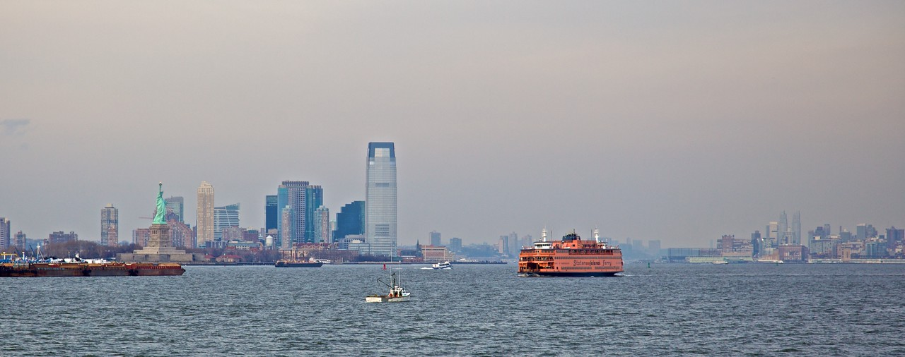 A Staten Island Ferry passes the Statue of Liberty as it travels toward Manhattan.