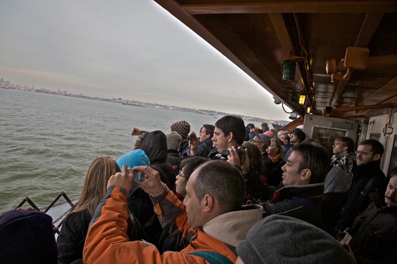 (Fellow-) Tourists on the open area at the end of the Staten Island Ferry, taking photos of the approaching Manhattan skyline.