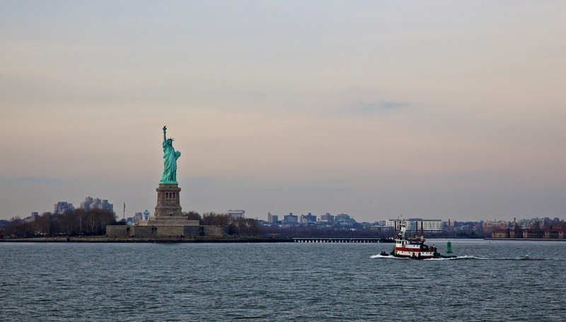 A trawler passes the Statue of Liberty.