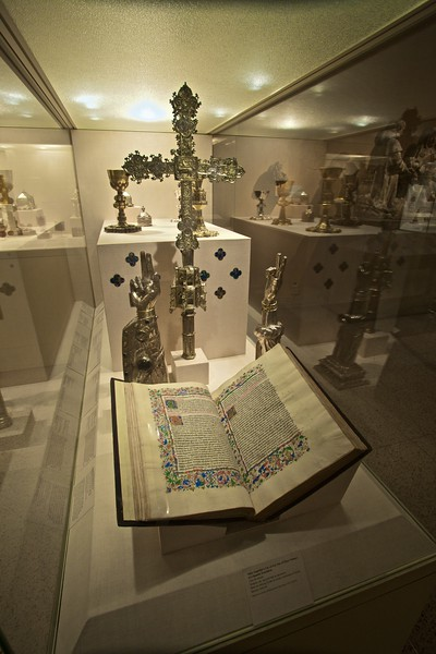 A silver reliquary in the shape of an arm (northern French, c. 1200–50), a gilded silver Processional Cross (Spanish, c. 1450), and one of three volumes of a Spanish translation of Augustine's <em>City of God</em>. (Met.)