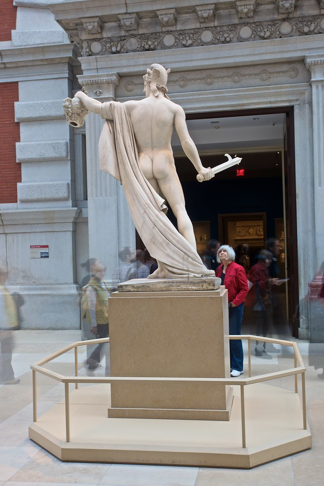 In the European Sculpture Court. (Met.)<br /> <br /> (Three photos blended together; the woman in the red coat was in the same position for all three photos while people walked past her.)