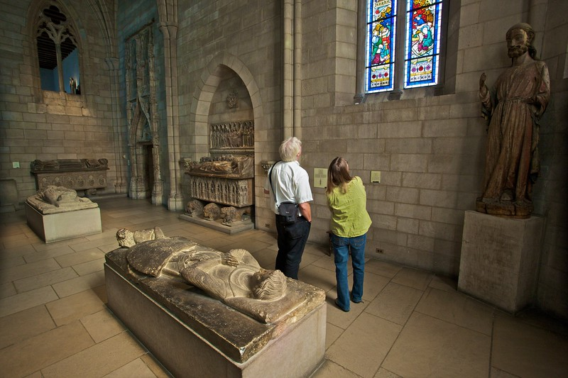 German tourists look at stained glass in the Gothic chapel. (Cloisters)