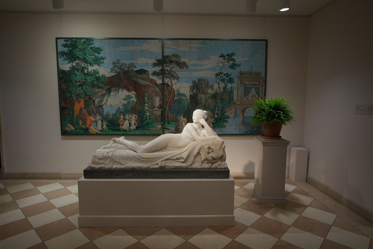 Statue of a reclining Naiad by Antonio Canova (1757–1822) in front of 'Promenade in a Barge' and 'Young girls dancing before a grotto', woodblock-printed wallpaper by the House of Dufour (c. 1820). (Met.)