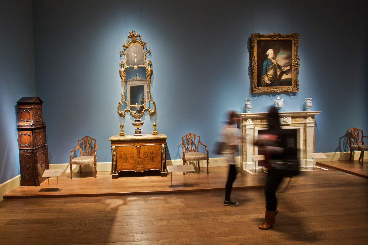 Visitors pass through a room filled with 18th-century English furniture. (Met.)
