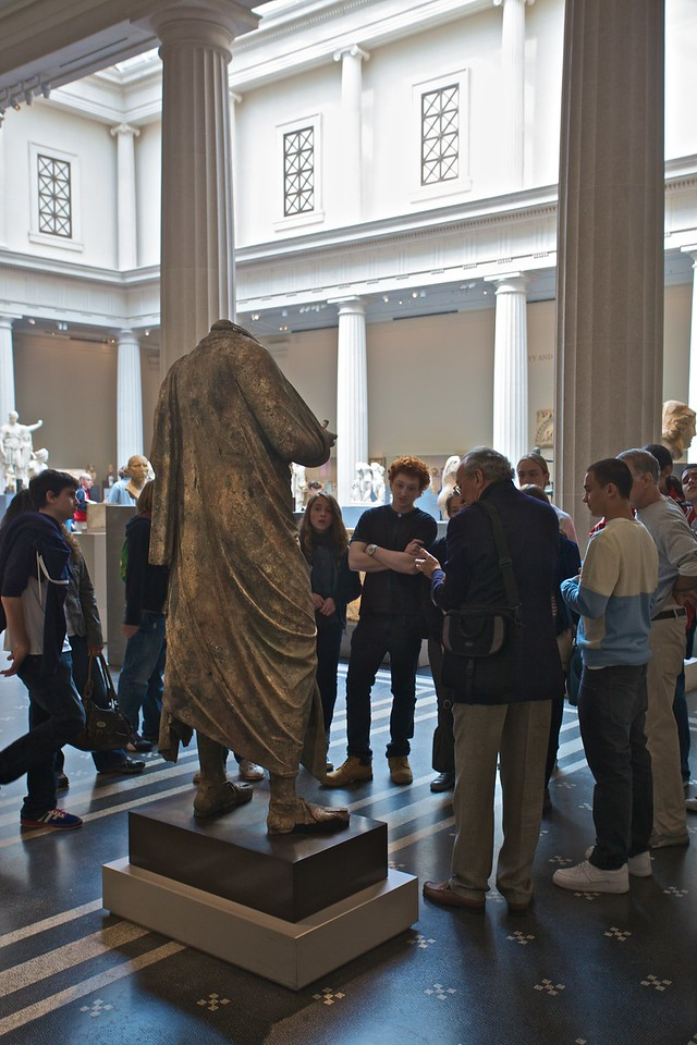 A school-group gathered around a Roman statue. (Met.)