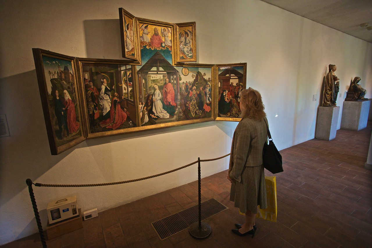 A woman looks at a mid-15th-century polyptych featuring the Nativity (S. Lowlands, Brabant, Brussels area). (Cloisters)