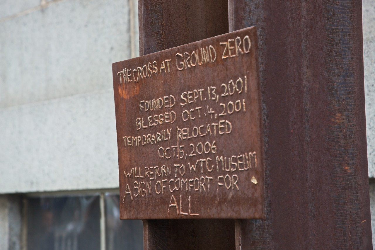 "This sign is attached to the <a href=""http://en.wikipedia.org/wiki/World_Trade_Center_cross"" title=""World Trade Center cross - Wikipedia, the free encyclopedia"">World Trade Center cross</a> near the site of the former WTC. The cross was found in the rubble following the terrorist attacks, and is in fact the junction of two prefabricated beams used in the construction of one or other of the twin towers."