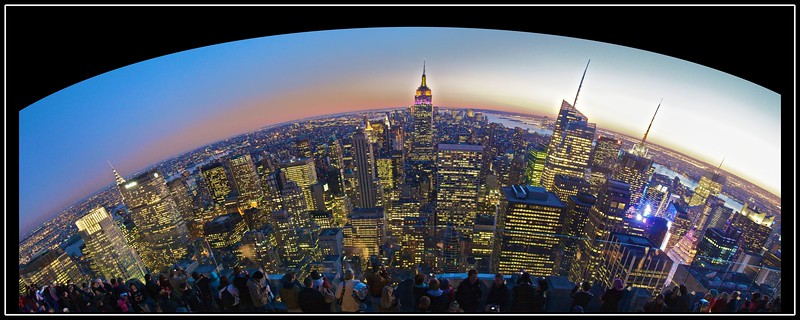 Panoramic photo of Midtown and Lower Manhattan at dusk as seen from the top of the GE Building (30 Rockefeller Plaza), looking due south. To the east (left) is the East River, on the other side of which are the boroughs of Brooklyn and Queens; to the west (right) is the Hudson River, beyond which is the city of Hoboken in New Jersey. If you know where to look, and are prepared to squint slightly, you can see the Statue of Liberty.<br /> <br /> Four frames stitched together. This is one of my absolute favourite photos of the trip, in spite of its various defects.