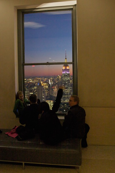 Tourists inside the viewing level of the GE Building looking over the Empire State Building.