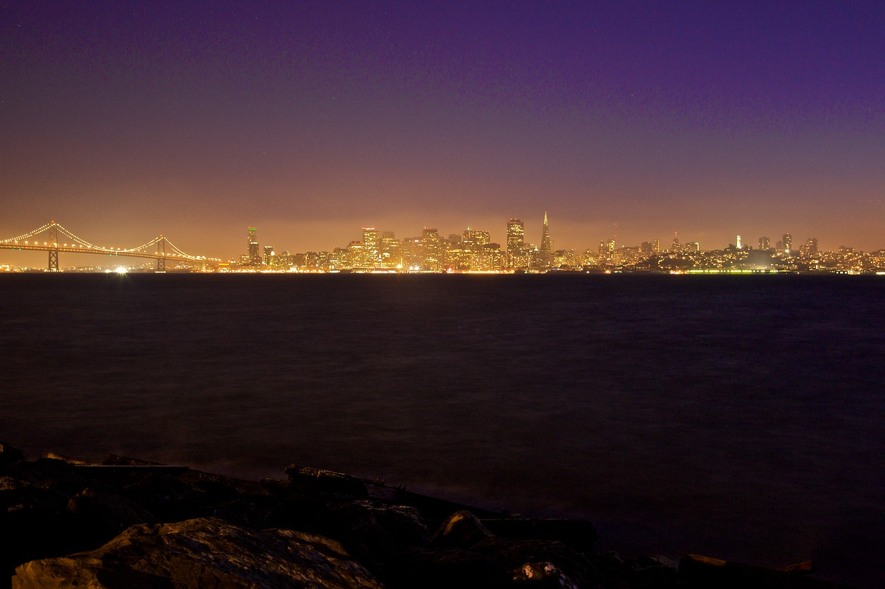 The lights of San Francisco and the Bay Bridge at dusk, as seen from Treasure Island.