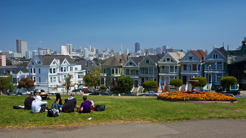 A group of French tourists picnicking in Alamo Square, from where there is an excellent view over the city of San Francisco.