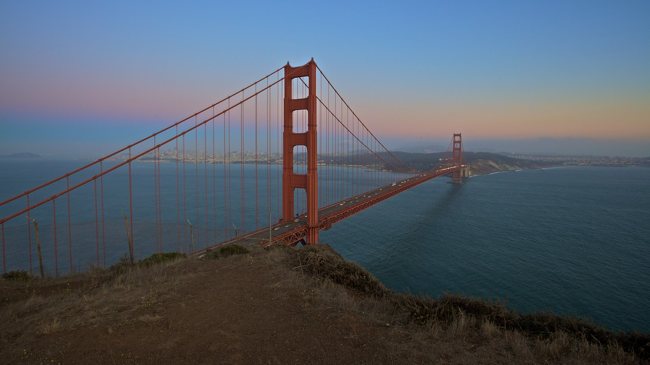 Traffic passing over the Golden Gate Bridge at dusk, as seen from the Marin Headlands on the bridge's north side.