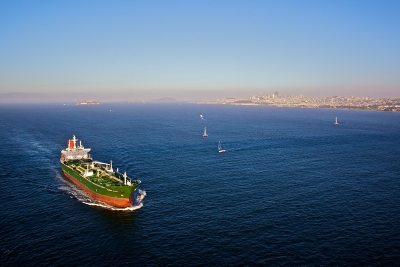The cargo vessel 'Golden State' passes underneath the Golden Gate Bridge. In the background you can see downtown San Francisco.