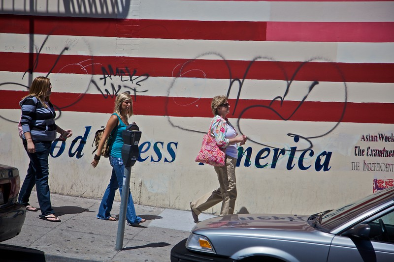 Women pass a painted-up, and subsequently defaced, American flag in Chinatown in San Francisco.