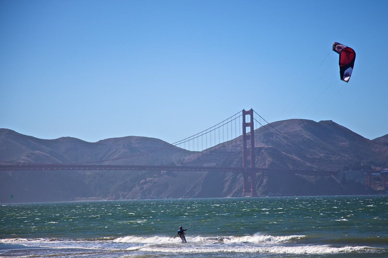 A wind-surfer takes advantage of the stiff breeze which comes into the San Francisco Bay from the Pacific. In the background you can see the north end of the Golden Gate Bridge, at the Marin Headlands.
