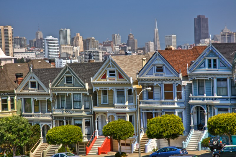 This is one of the most famous postcard views of San Francisco: the houses are even often informally dubbed 'Postcard Row'. The 'Painted Ladies'—Victorian houses along Alamo Square which were mercifully spared by the Great Earthquake of 1906—are seen in front of the modern buildings of downtown San Francisco, including the Transamerica Pyramid.