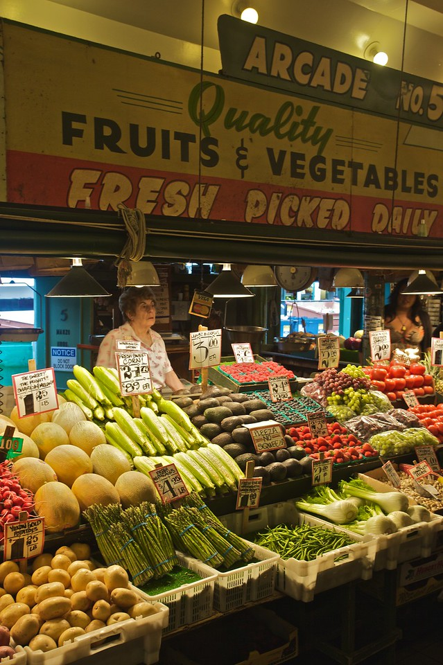 A woman sells fruit and vegetables from her stall in Pike Place Market in Seattle.