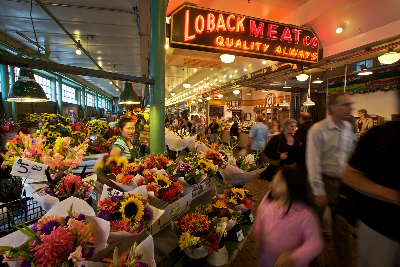 A woman sells flowers as customers rush past in Pike Place Market in Seattle.