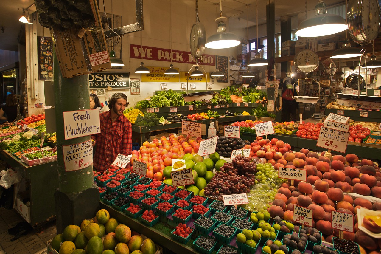 A man hawks his fruit for sale in Pike Place Market in Seattle. I am particularly excited that 'Razz Berries' are on special offer.