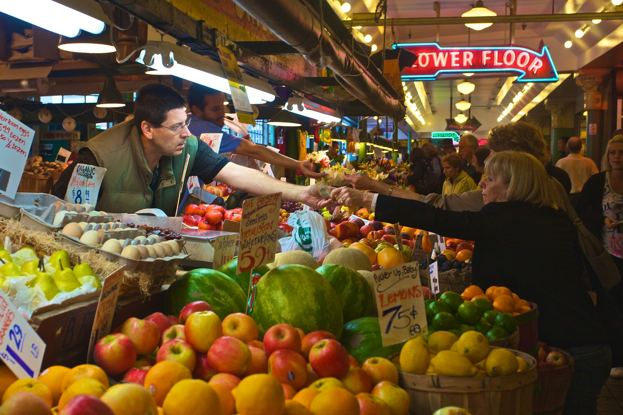 Two women hand over money to pay for their fruit bought from a stall in Pike Place Market.