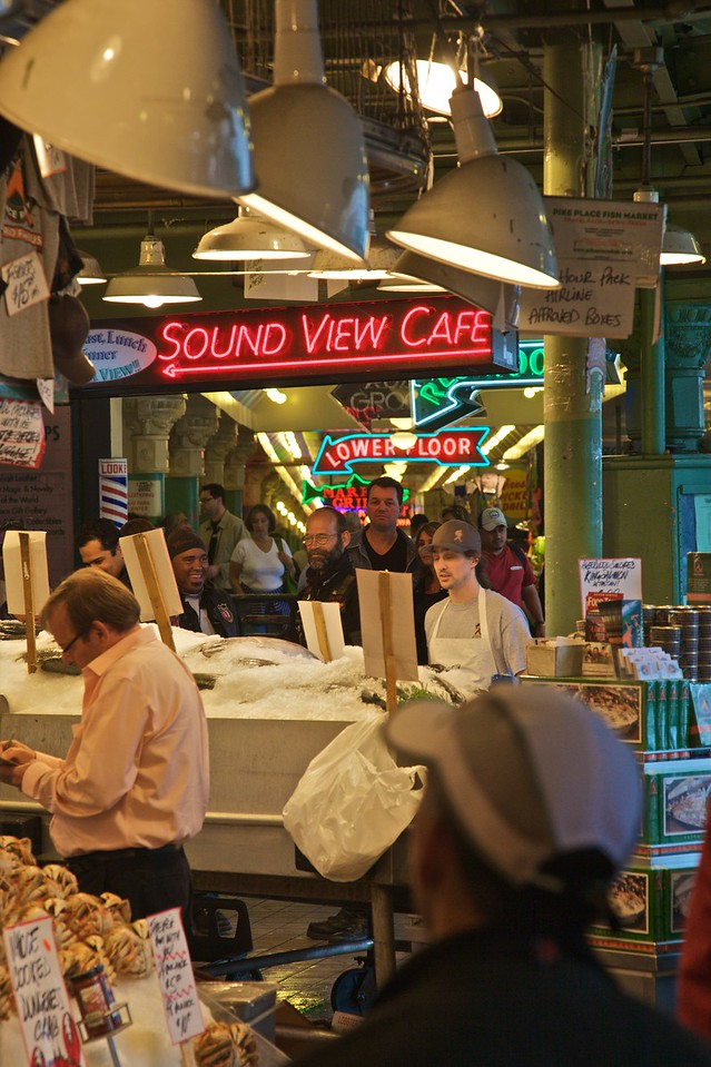 Customers and neon signs in the Pike Place Market in Seattle.