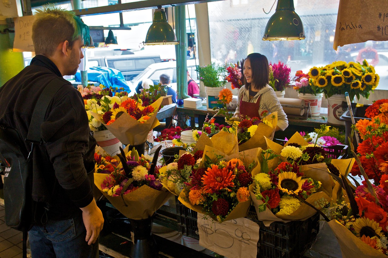 A customer buys flowers in Pike Place Market in Seattle.
