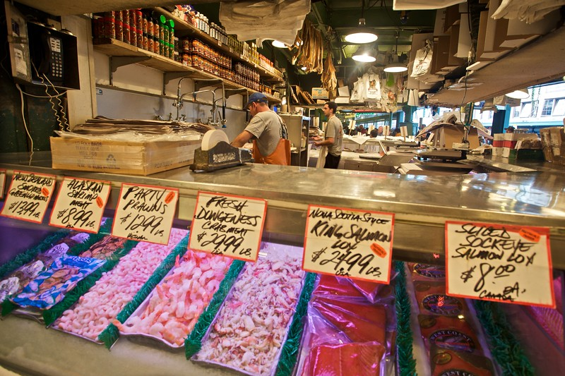 Two men at work at their seafood stall in Pike Place Market in Seattle.