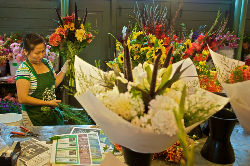 A woman prepares a bouquet of flowers for sale in Pike Place Market in Seattle.