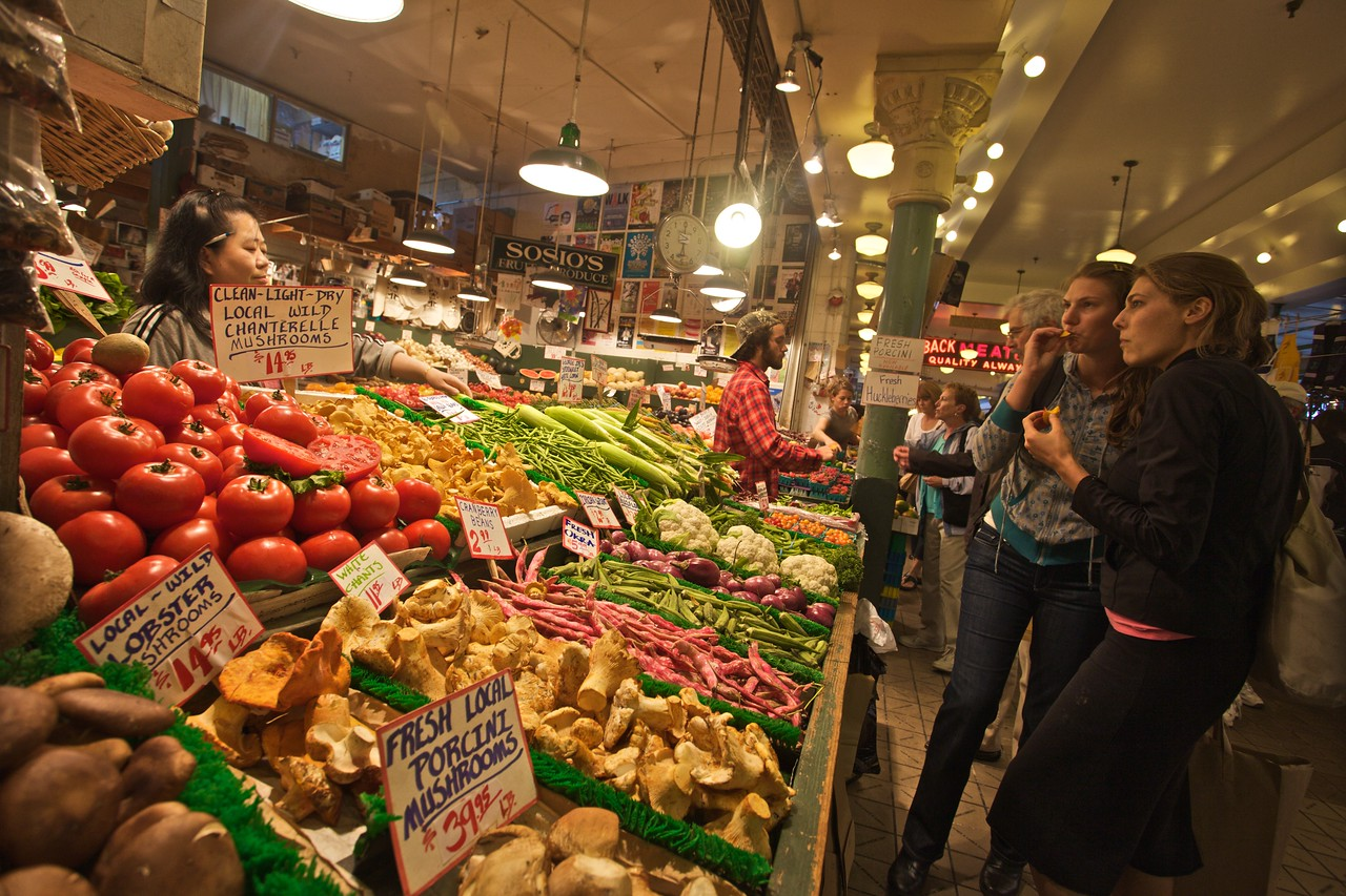 Two women sample mushrooms for sale in Pike Place Market in Seattle.