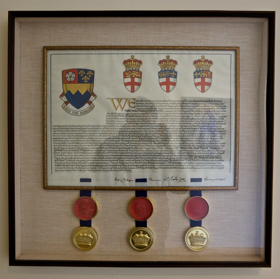 The Grant of Arms from the College of Arms to the Priory of St Mary and St Louis. The St Louis coat of arms is obviously intended to mimic that of Ampleforth. Where Ampleforth's arms have the Thames, St Louis' arms have the Mississippi. The crossed keys of Peter have been replaced with a Yorkshire rose, and the cross and marlets of St Edward the Confessor have been replaced with Fleur de Lys of royal France (because of the patronage of St Louis).