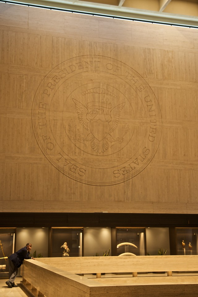 A museum official lolls beneath the enormous carved presidential seal in the Lyndon Johnson museum in Austin.