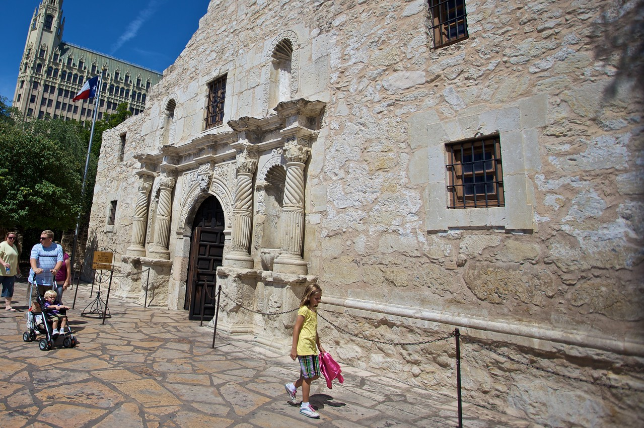 Tourists strolling in front of the Alamo.