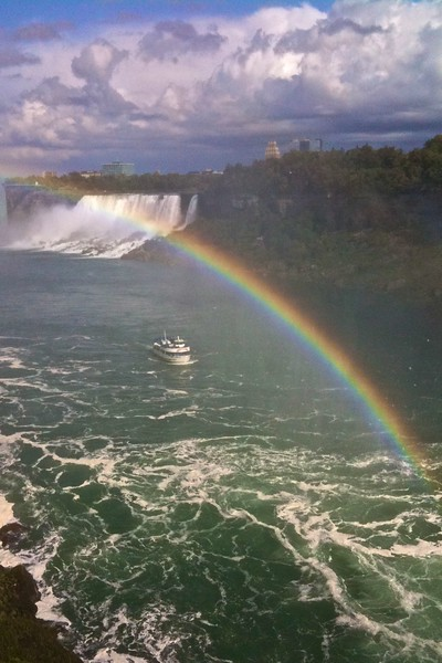 Post tenebras lux (pace Calvin): a rainbow crosses the Niagara River at Niagara Falls after a particularly heavy rain-shower, with the <cite>Maid of the Mist</cite> passing beneath it as she approaches the Canadian Falls. In the background you can see the American Falls. This wasn't the end of the rain for the day, however: less than an hour later I took the boat journey and was drenched on the deck before we were anywhere near the falls (which then dumped even more water over everyone).  (Photo taken with my iPhone because by this point my main camera had died an untimely death. I am pleased to report that it has since been revived by Canon technicians, however.)