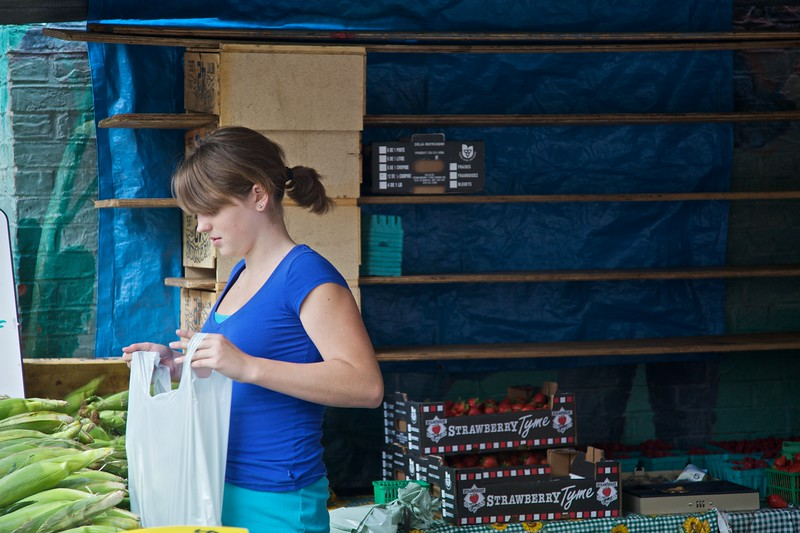 A girl bags up groceries for sale at a stall in the St Lawrence Markets in Toronto. I don't think she cosciously co-ordinated her clothing with the tarpaulin behind her place of work: it was merely chance.