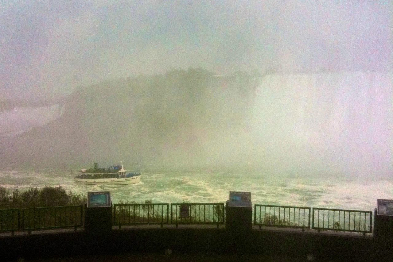 The <cite>Maid of the Mist</cite> approaches the Canadian Falls at Niagara Falls in billowing rain. In the background at the left of the photo you can see the edge of the American Falls. This photo is taken from a viewing platform accessed via the 'Tunnels behind the Falls': at this point I was at a level about half-way down the Canadian Falls, and was getting very wet (mainly from the exceedingly heavy rain).  (Photo taken with my iPhone because by this point my main camera had died an untimely death. I am pleased to report that it has since been revived by Canon technicians, however.)