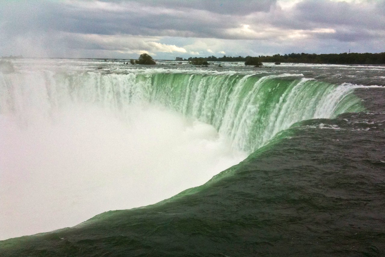 "Water escaping across the Canadian, or Horseshoe, Falls, the most famous sight at Niagara Falls. The drop is about 52 metres, and the Canadian Falls are about 650 metres across. The <cite>Rough Guide</cite> describes the falls as 'a perpetual white-crested thundering pile=up that had Mahler bawling ""At last, fortissimo,"" over the din.'  (Photo taken with my iPhone because by this point my main camera had died an untimely death. I am pleased to report that it has since been revived by Canon technicians, however.)"
