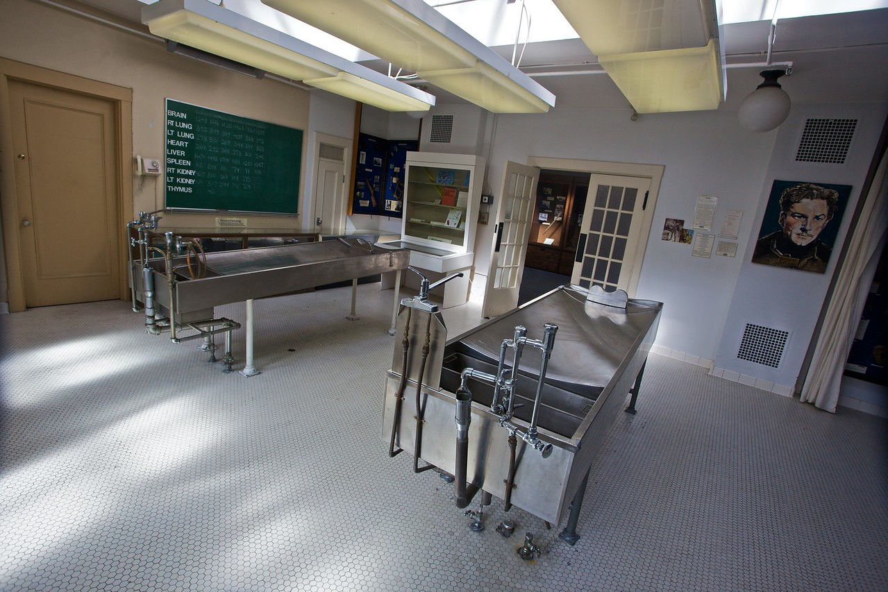 "The autopsy room of the former morgue now contained within the Police Museum of Vancouver. The portrait at the right of the frame is of my distant relative Errol, whose body was autopsied in this room after he died in 1959.  <blockquote>""Flynn arrived in the city in October 1959 with his best acting days well behind him. With him was his 'personal assistant', a 17-year-old blonde girl not known for her secretarial skills. Within two days Flynn had dropped dead in his rented West-End apartment. The body was brought to the Coroner's Court, where the pathologist conducting the autopsy is said to have removed a piece of Flynn's penis and placed it in formaldehyde to keep as a souvenir. The horrified chief coroner Glen McDonald, a rather more fastidious operator, is said to have pulled rank and reattached the missing piece of member to the corpse with sticky tape. The body was then dispatched to Los Angeles for burial. [etc.]"" <cite>—<cite>Rough Guide to Canada</cite></cite></blockquote>"