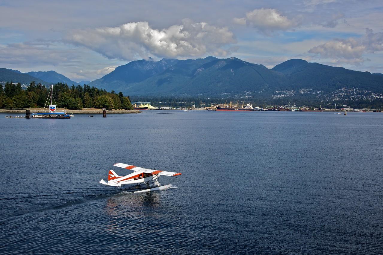 A seaplane lands on Burrard Inlet (Vancouver harbour).