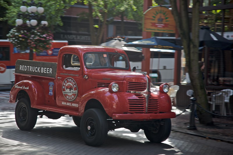 A red truck advertising Red Truck Beer passes through Gastown in Vancouver.