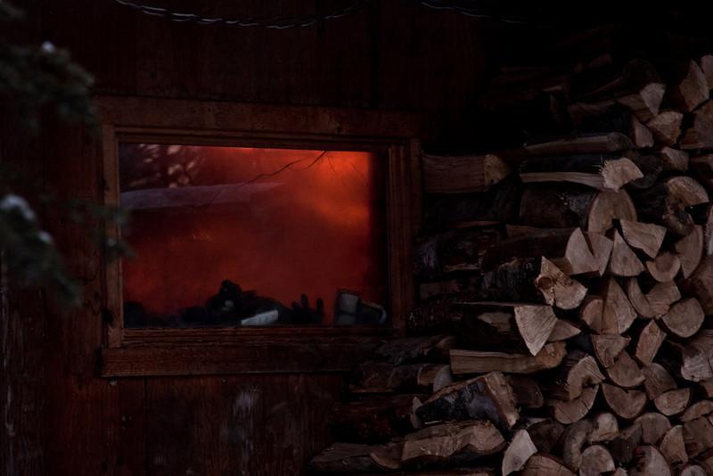 Fire glows through a smoky window.