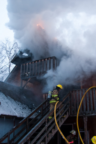 Small tongues of flame remain on the eaves of the roof as crews get the fire on the interior knocked down.