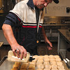Tribune-Star/Joseph C. Garza<br /> A thanksgiving staple: Lighthouse Mission cook Bill Wilson makes dinner rolls a bit more delicious with seasoning before serving the Thanksgiving dinner at the Lighthouse Mission Thursday.