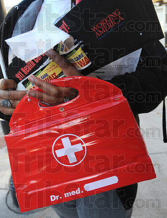 """First aid: A Working America volunteer carries a first aid kit and literature about the """"public option"""" plan being considered by congress. They offered cell phones and numbers to anybody that wanted to call their congressman or senator and ask him to vote in favor of the """"public option"""" plan."""