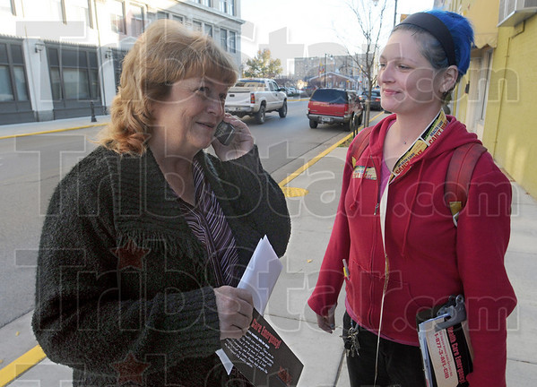 Can you hear me now: Terre Haute resident Sandy Swift uses a cell phone and telephone number provided to her by Bonnie Schafman at the corner of 7th and Wabash Thursday afternoon. Schafman is an organizer with Working America.