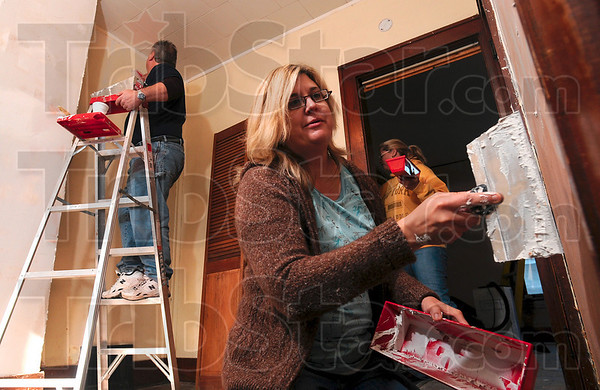 Tribune-Star/Joseph C. Garza<br /> Making it a home: Home owner Peggy Wesley-Fitzthum quickly works on spackling in the home at 720 Elm Street with volunteers Tom and Lisa Moore, in background, Sunday in Clinton. The volunteers are preparing the home for widow, Mary Kennedy and her two children.