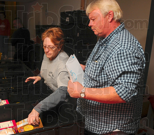 Tribune-Star/Joseph C. Garza<br /> For a better Thanksgiving: Club Soda volunteers Kathy Kiger and Rich Gartzke keep track of what food items have been added to several baskets Sunday at Club Soda.
