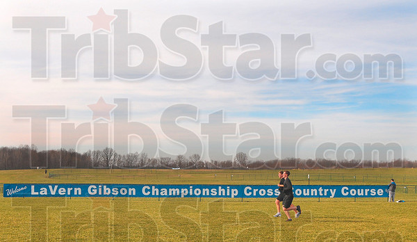 Tribune-Star/Joseph C. Garza<br /> It will crown a champion: A pair of runners try out the Lavern Gibson Championship Cross Country Course as Dan O'Brien, right, of the Indiana State Athletic Department hangs a banner Sunday at the course.