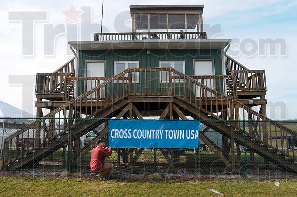 Tribune-Star/Joseph C. Garza<br /> On the map: Indiana State assistant track and cross country coach Adam Judge hangs a sign on the Lavern Gibson Championship Cross Country Course Sunday in preparation for today's NCAA Division I Championships.